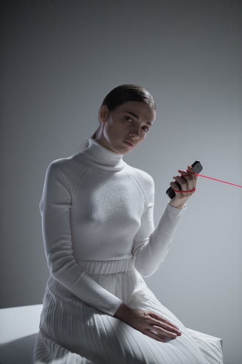 Woman in White Turtleneck Sweater Holding Red and Black Stick