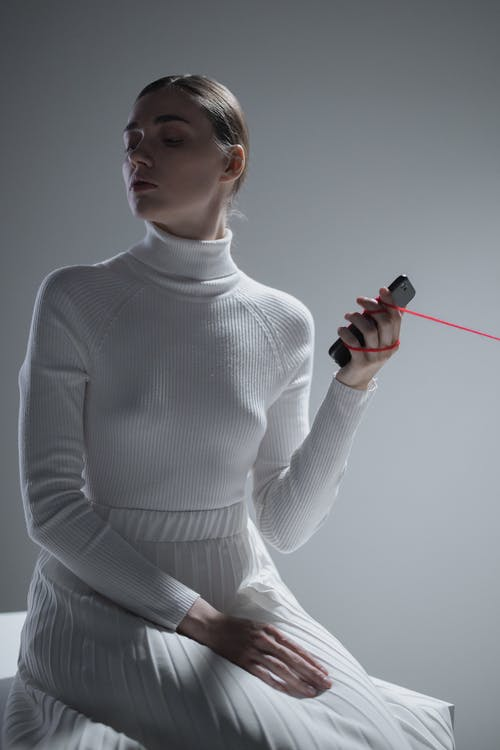 Man in White Turtleneck Sweater Holding Red and Black Hand Tool