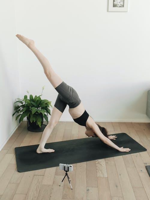 Woman in Black Sports Bra and Black Shorts Doing Yoga on Black Mat
