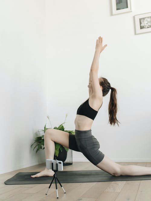A Woman Recording Herself While Doing Yoga