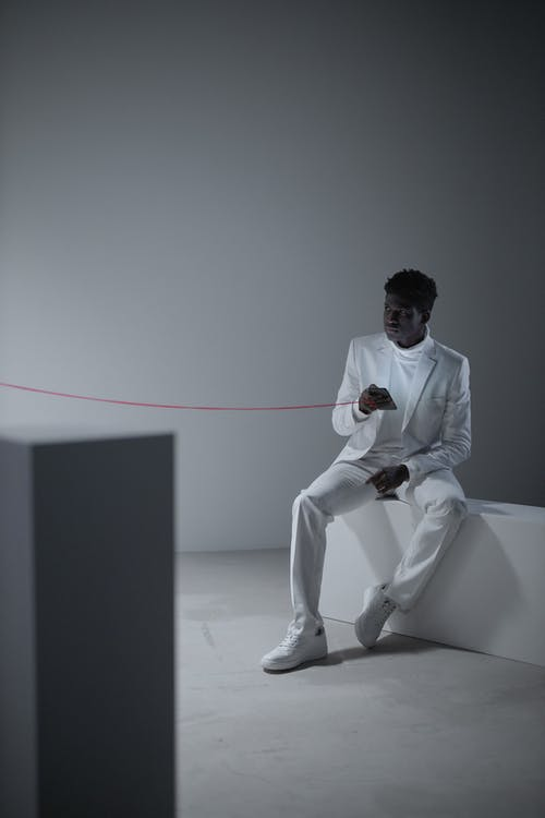Man in White Dress Shirt and White Pants Sitting on White Chair