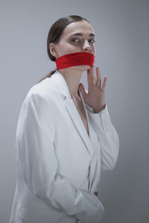 Woman in White Button Up Long Sleeve Shirt With Red Plastic Cover on Face