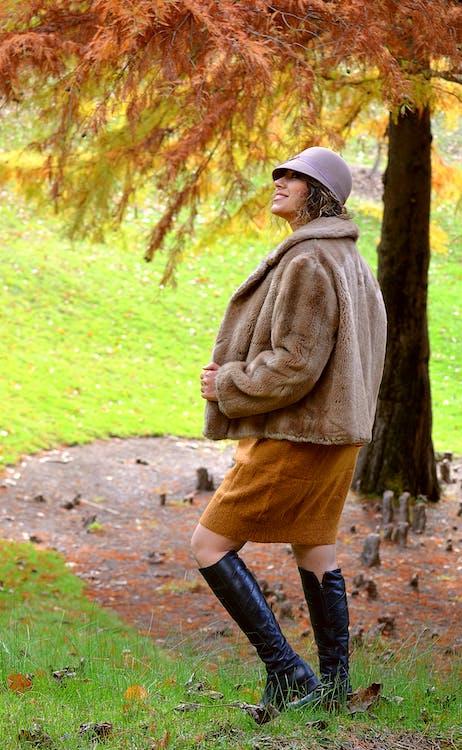 Woman in Brown Coat Walking on Pathway