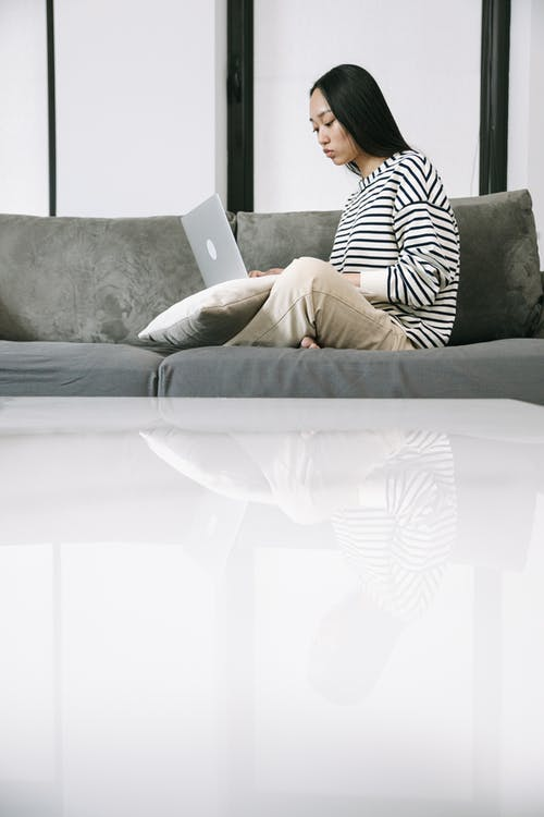Woman Sitting on Sofa while Using a Laptop