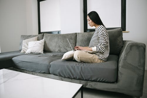 Woman in Black and White Stripe Shirt Sitting on Gray Couch