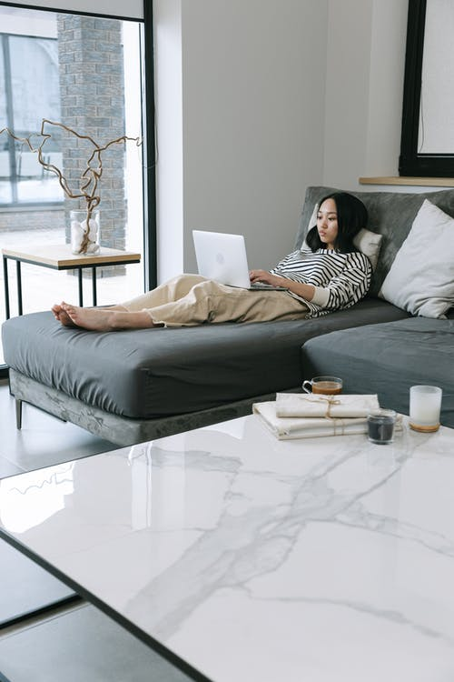 Woman Lying on Sofa while Using a Laptop