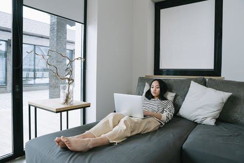 Woman Lying on Gray Couch Using Macbook