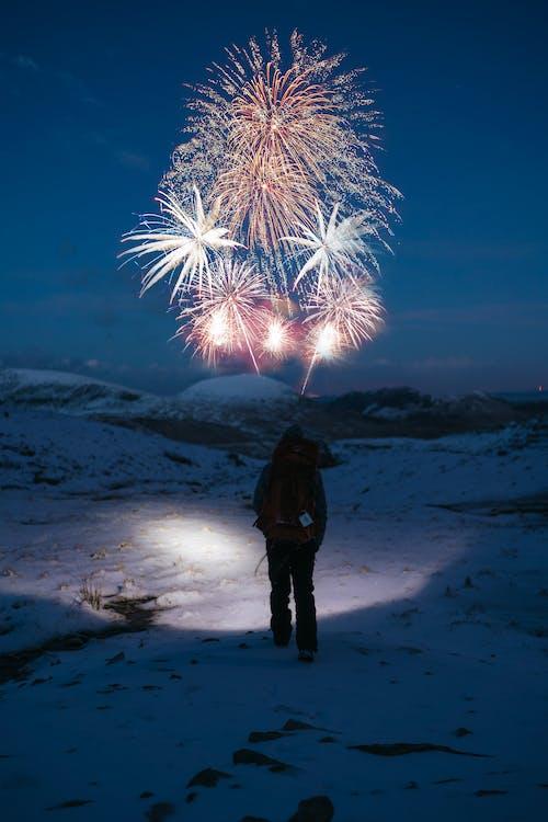 Osoba Stoi Na Pokrytej śniegiem Górze Patrząc Na Fajerwerki