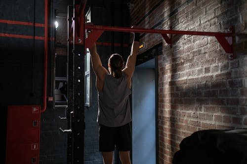Man in White T-shirt and Black Shorts Standing on Red Metal Bar