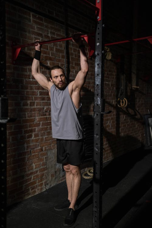Man in Gray Tank Top Holding onto a Pull-Up Bar
