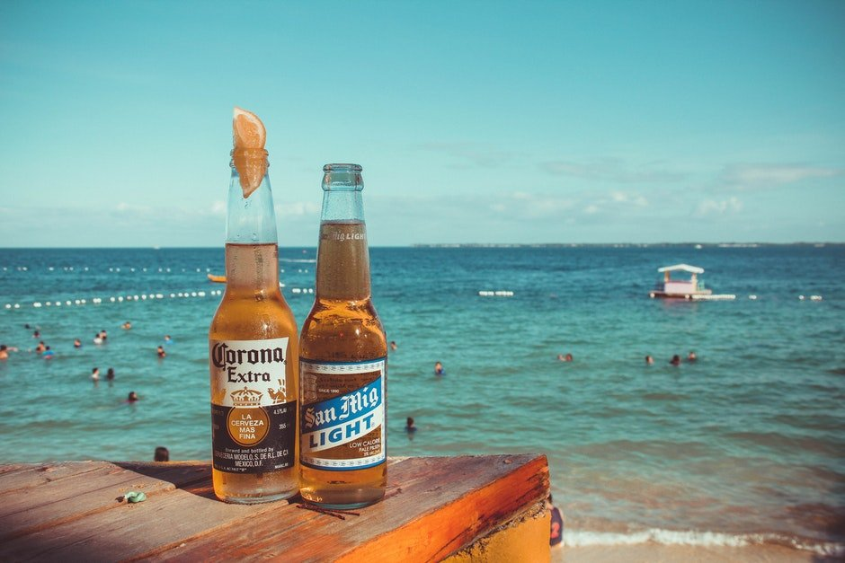 Two Corona Extra and San Mig Light Beers on Top of Brown Wooden Plank Near Beach