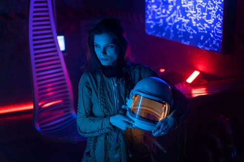 Woman in Spacesuit Holding A Helmet