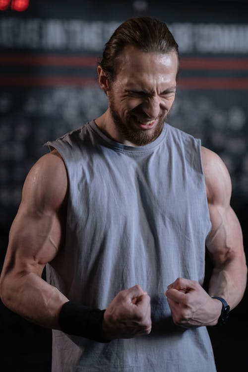 Man in Gray Tank Top Flexing His Muscles