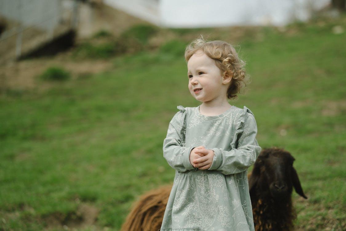 Girl in White Dress Standing Beside Brown Horse