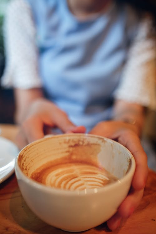 Soft focus of crop unrecognizable female sitting at table with cup of hot coffee with latte art in light cafe