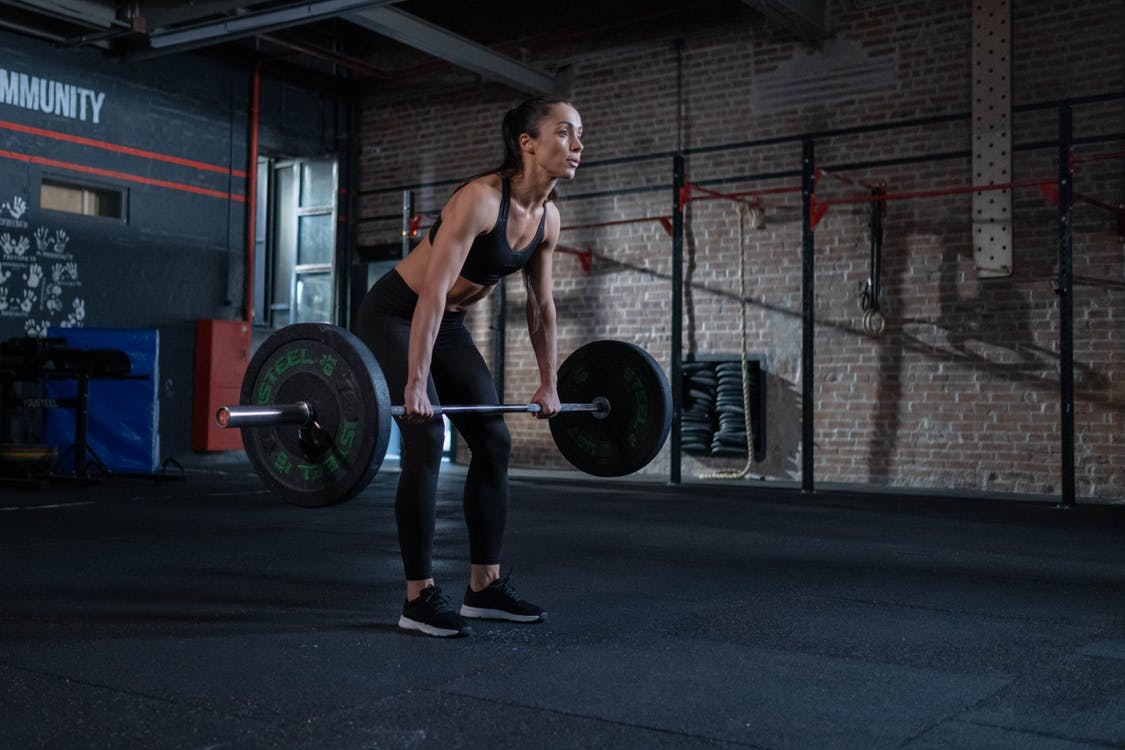 Woman in Black Sportswear Lifting a Barbell