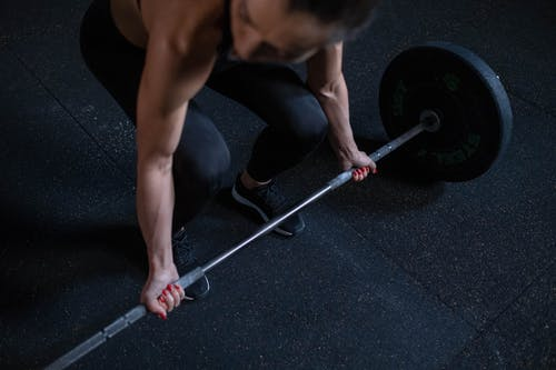 High-Angle Shot of a Woman Lifting a Barbell