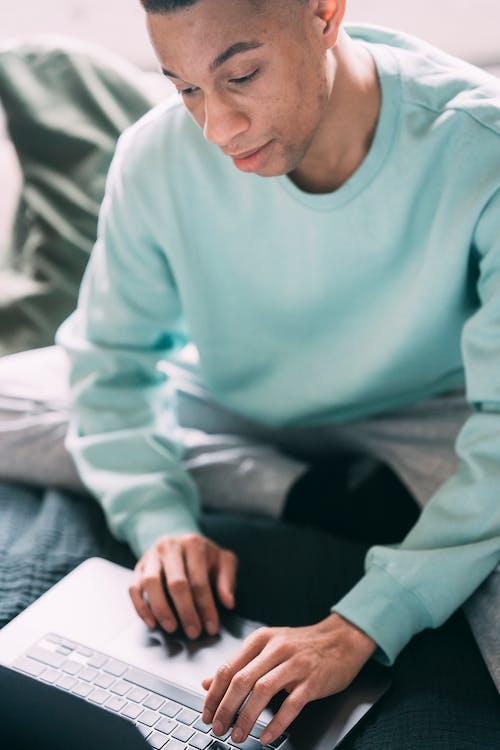 Focused black man browsing laptop