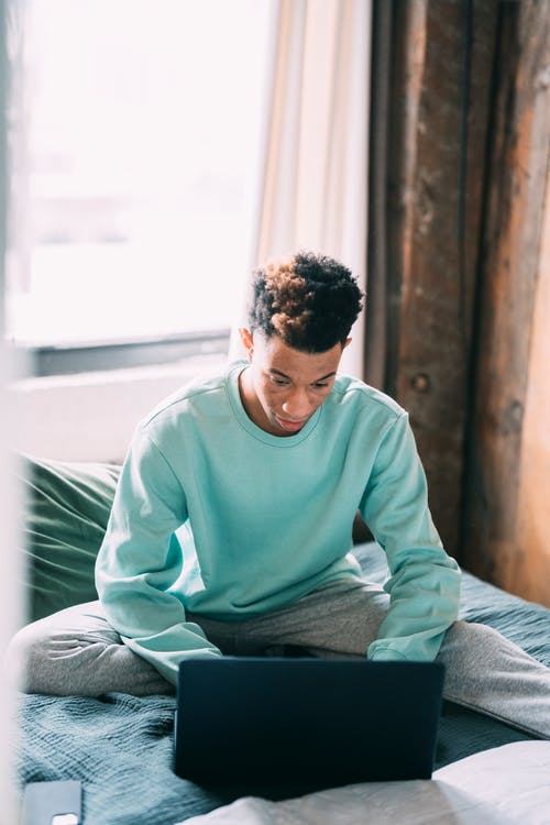 Serious black man surfing laptop in bedroom