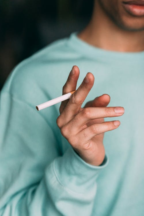 Unrecognizable man with cigarette in hand