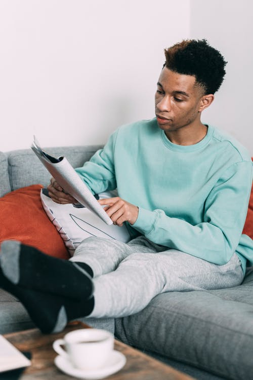 Serious black man reading magazine on couch
