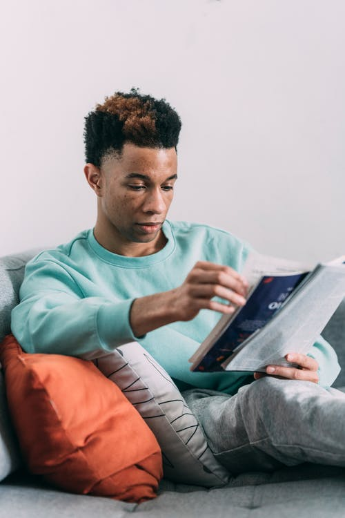 Concentrated African American male reading interesting magazine while sitting on comfortable sofa on white background in light room at home