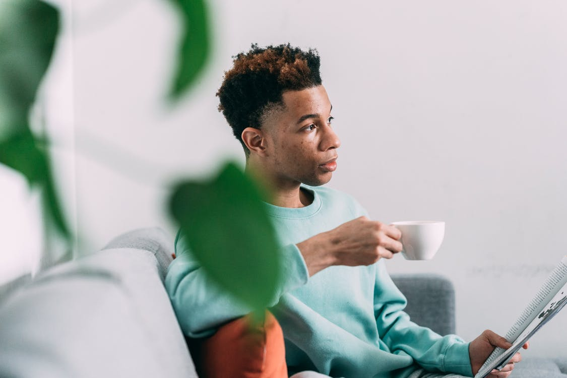 Side view of serious African American male drinking coffee while reading magazine on couch in light living room with blurred plants
