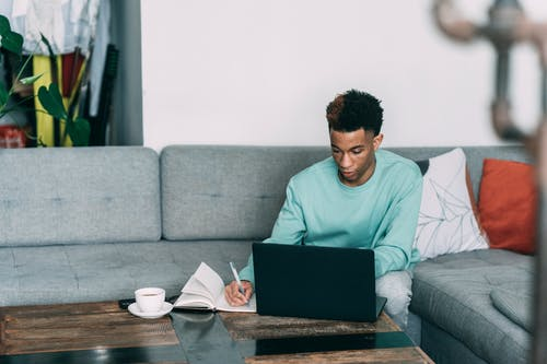 Thoughtful black man with laptop writing in notebook