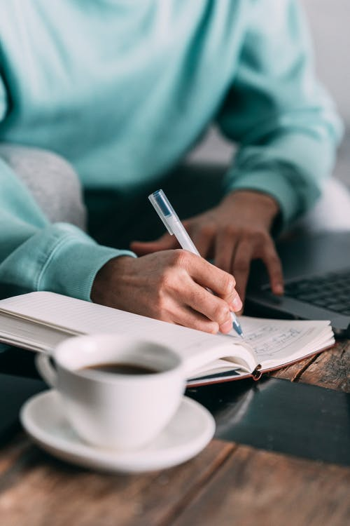 Crop anonymous male freelancer taking notes in notepad while sitting at wooden table with laptop and cup of coffee at home