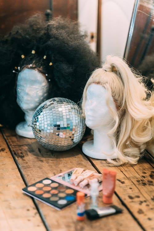 Wigs on mannequins near sparkling disco ball and palette