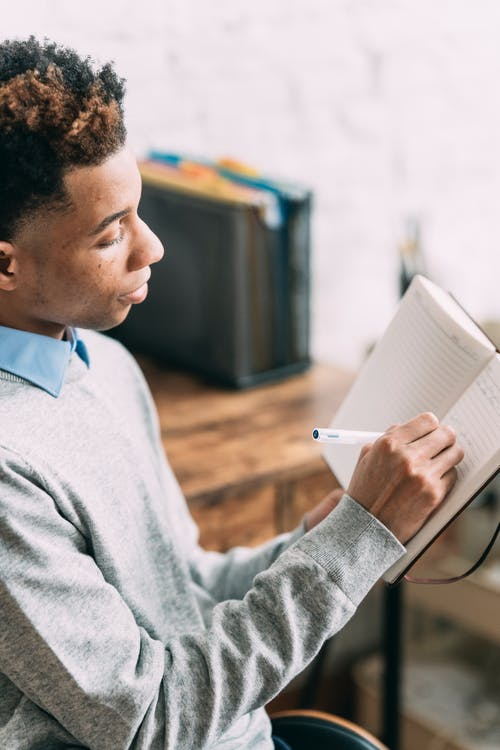 Black man taking notes in empty planner at home