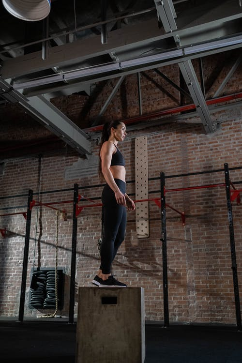 Woman in White Tank Top and Black Pants Standing on Brown Wooden Ladder