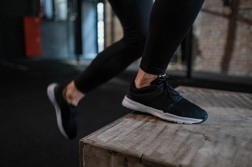 Person in Black Pants and Black and White Nike Sneakers