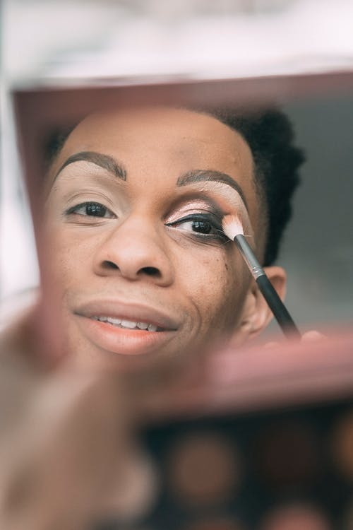 Soft focus of feminine African American male looking at mirror of palette while applying eyeshadow with brush in light room