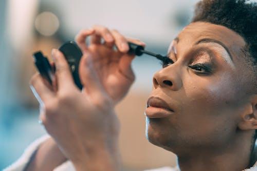 Feminine black man applying mascara on eyelashes