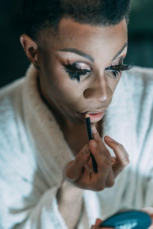 Feminine African American male with dark hair in white bathrobe with eyelashes applying lip pencil on lips in dressing room
