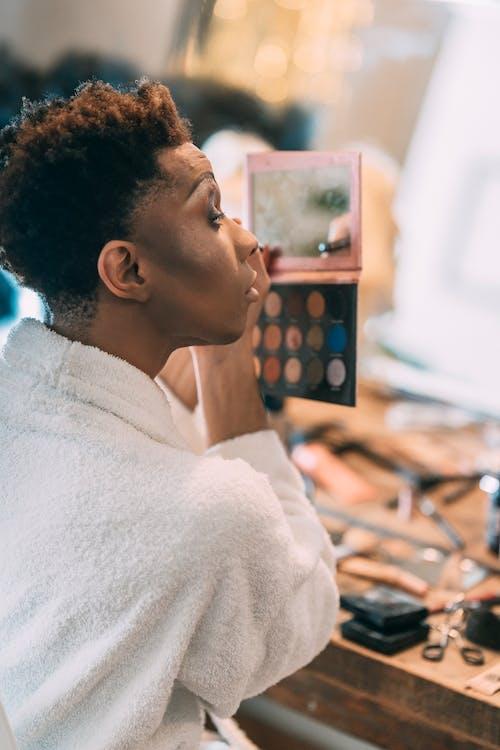 Eccentric black man applying makeup