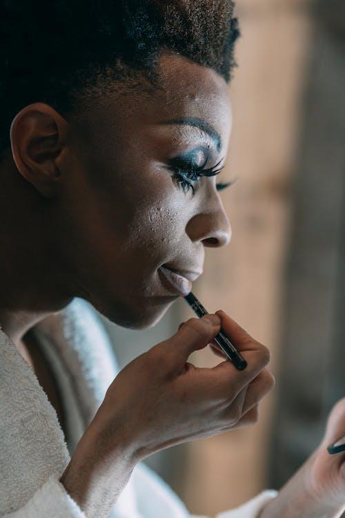 Eccentric black man with lip pencil