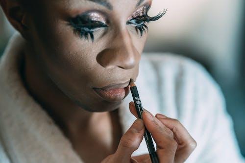 Black man with makeup applying lip pencil