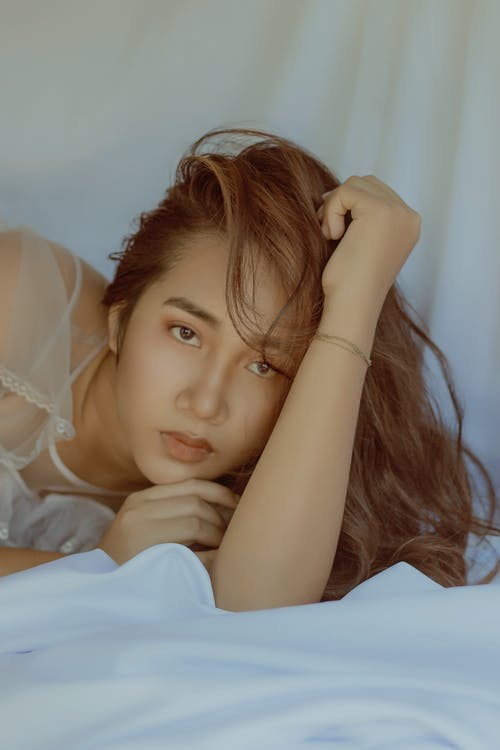 Attractive Asian woman lying on cozy bed