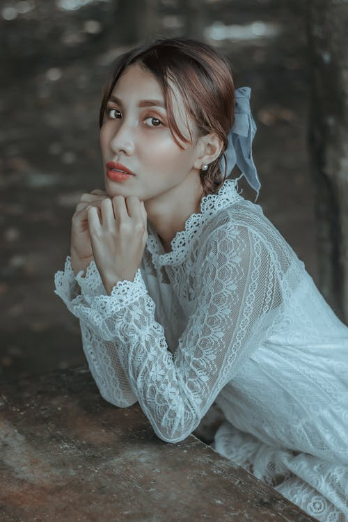 Sensitive young ethnic female wearing white lace dress leaning on hands and looking at camera while sitting at weathered wooden table in garden