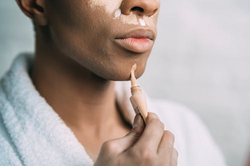 Crop anonymous African American man doing facial makeup with foundation cream as drag queen