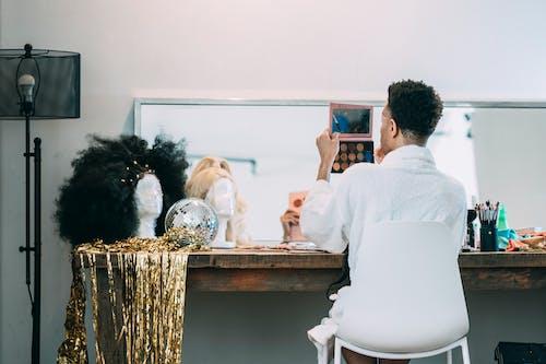 Unrecognizable man doing makeup in dressing room