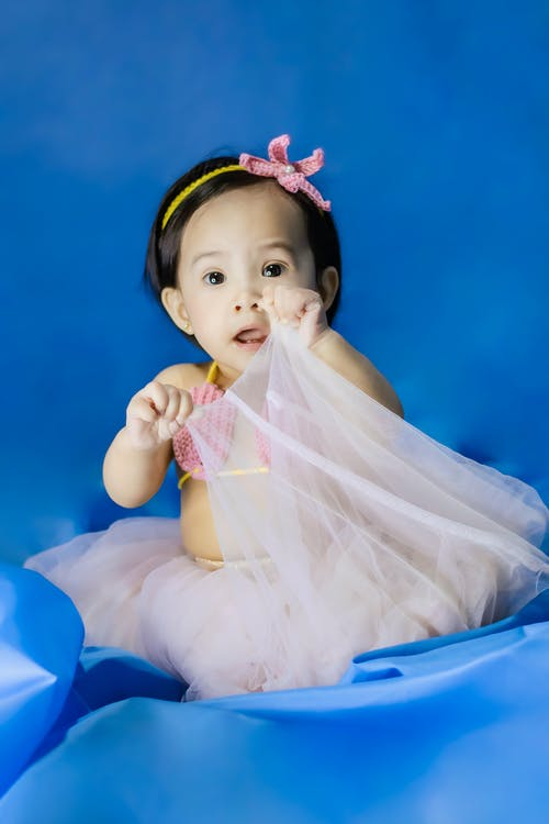 Full body of adorable little Asian girl with dark hair in stylish swimwear and tutu skirt looking at camera against blue background in studio
