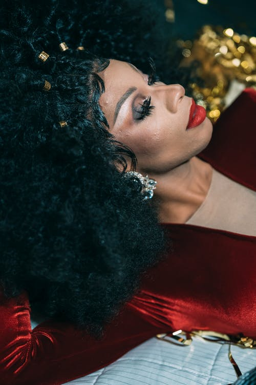 Gorgeous African American drag queen with bright makeup and hairstyle in fashionable clothes lying with closed eyes and leaning on hand in during performance in festive studio