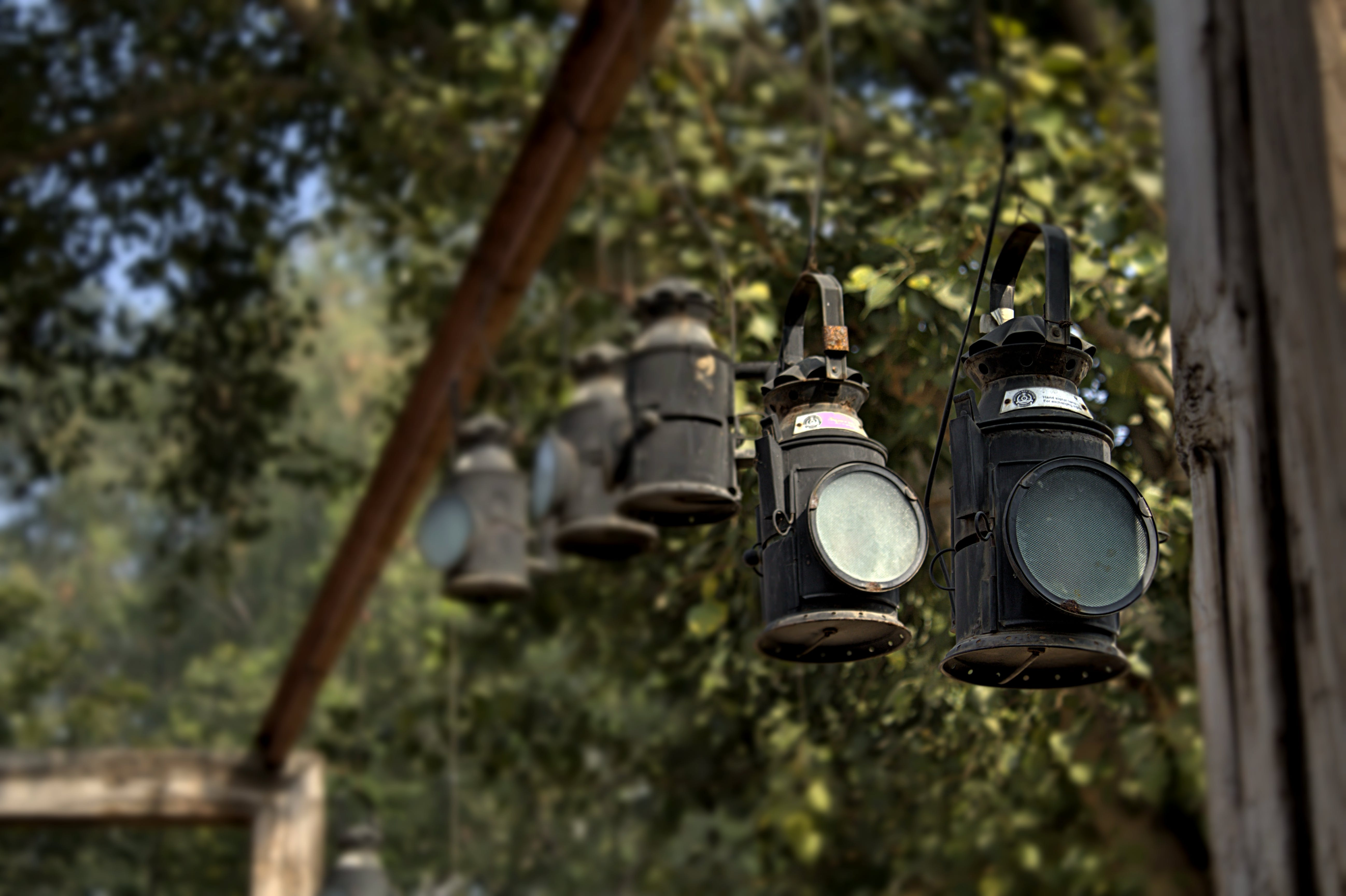 Black Metal Lanterns Hanged in Brown Wooden Frame