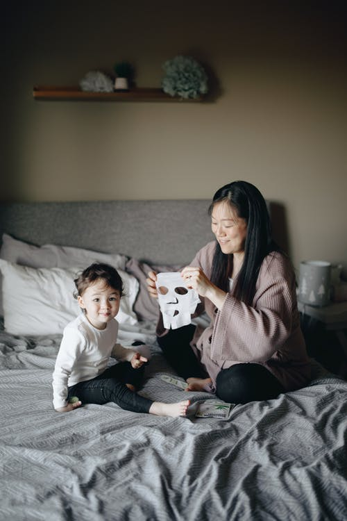 Mother Holding A Mask While Sitting On Bed With Her Child