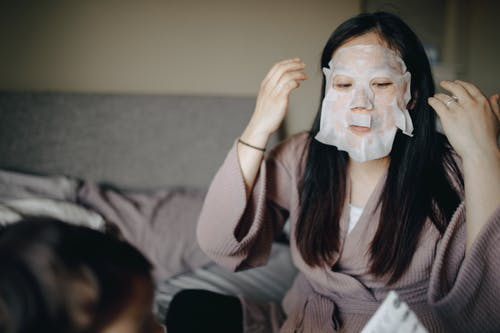 Woman in Gray Sweater Covering Her Face With Mask