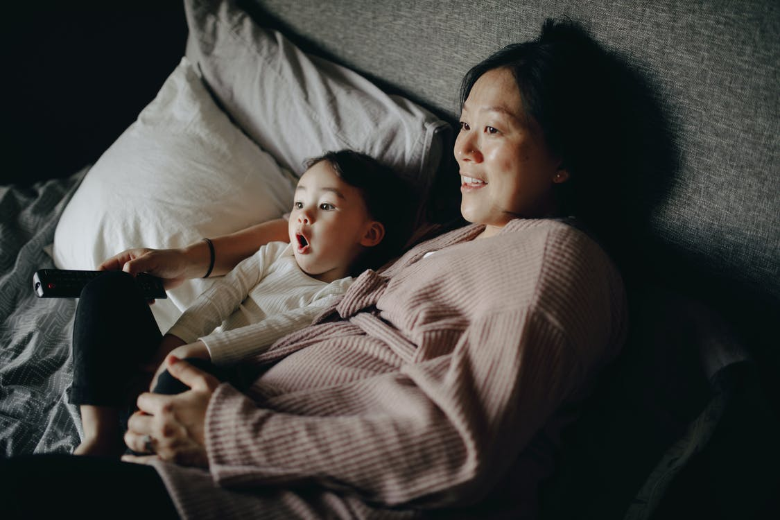 Mother And Child Lying On Bed