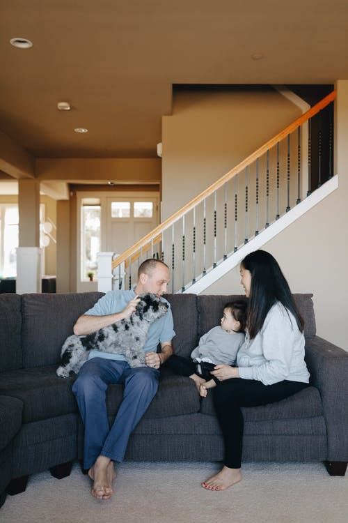 Family Sitting On Gray Sofa With Their Pet Dog